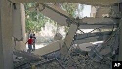 图为儿童8月4日在迪黎波里以东的城镇兹利坦翻越一所被炸毁学校的围墙