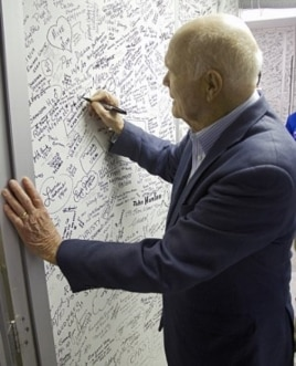 John Glenn signs the wall of the clean room leading into space shuttle Discovery in Orbiter Processing Facility-1 OPF-1 at NASA's Kennedy Space Center in Florida. Glenn is at the space center to mark the 50th anniversary of being the first American astron