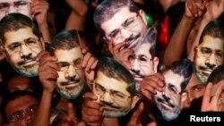 Članovi Muslimanskog bratstva drže Morsijeve maske na protestu u Kairu, 12. jul 2013.