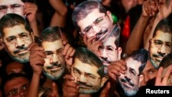 Adeviye Meydanı'nda Mursi maskeleri takan Mısırlılar