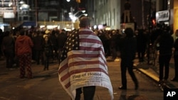 A man carries an American flag while walking to join a crowd gathered to celebrate the death of Osama bin Laden at the construction site at Ground Zero in New York, May 2, 2011.