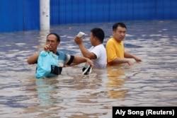 People wade through a flooded road following heavy rainfall in Zhengzhou, Henan province, China July 22, 2021.