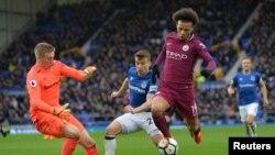Leroy Sane de Manchester City essaie de dribbler le gardien d'Everton, Angleterre, le 31 mars 2018.