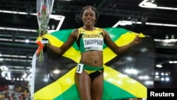 FILE - Elaine Thompson of Jamaica celebrates her bronze medal finish in the women's 60 meters final during the IAAF World Indoor Athletics Championships in Portland, Oregon, March 19, 2016.