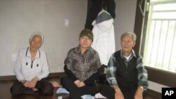 Han Bok-yeo (center) and her two neighbors from Seo-Yeonpyeong Island sit together in their apartment in Gimpo, South Korea