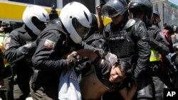 Polisi Ekuador menangkap seorang demonstran di luar Majelis Nasional, yang sedang membahas reformasi-reformasi konstitusional yang dianggap melawan hak-hak suku asli, serikat dan kelompok sosial. (Foto: Dok)