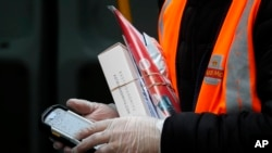 In this March 5, 2020, photo, a Royal Mail employee wears gloves as he hold parcels and the signature handheld as he delivers in London.