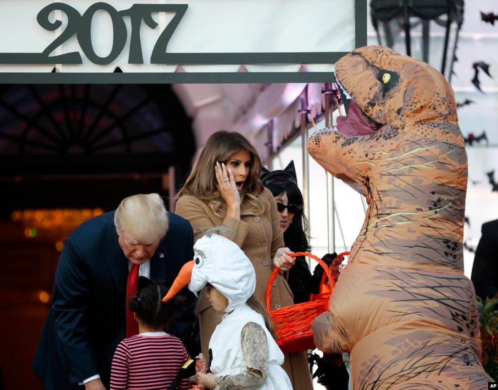 President Donald Trump and first lady Melania Trump hand out treats as they welcome children from the Washington area and children of military families to trick-or-treat celebrating Halloween, Oct. 30, 2017.