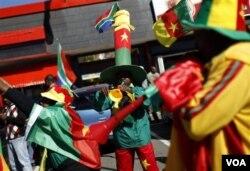 Para pendukung Kamerun meniupkan instrumen khas Afrika Selatan, 'vuvuzela,' di depan Stadion Free State di Bloemfontein.