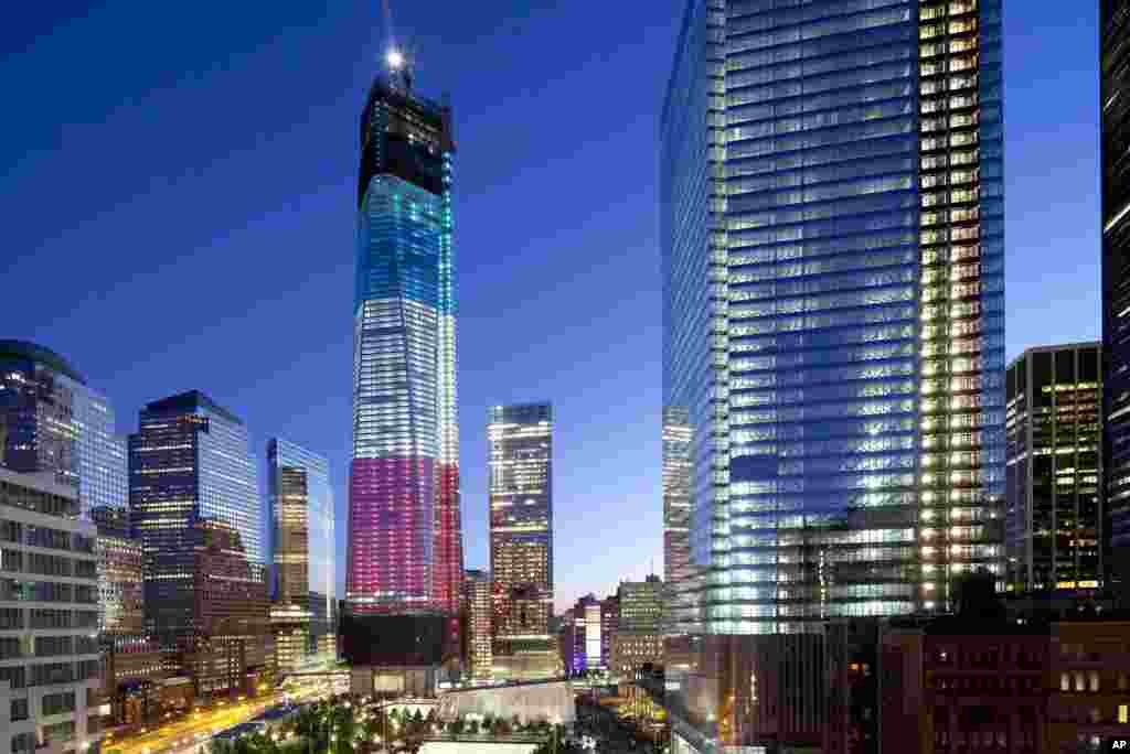 The tower known as 1 World Trade Center, left, the National September 11 Memorial, bottom left, and 4 World Trade Center, right, are bathed in light, New York, September 11, 2012.