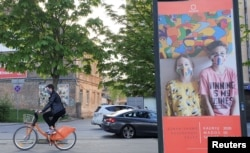 "A bicyclist rides next to a billboard, a part of a ""Mask Fashion Week"" during the coronavirus disease (COVID-19) outbreak in Vilnius, Lithuania May 5, 2020. REUTERS/Andrius Sytas"