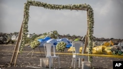 Wreaths and floral installations stand next to piles of wreckage where an Ethiopian Airlines Boeing 737 Max 8 crashed shortly after takeoff on Sunday, killing all 157 on board.