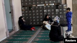 Syrian women rest at the entrance of a mosque in the neighborhood of Basmane, which is filled with transient migrants on their way to Europe, in the Aegean port city of Izmir, western Turkey, March 8, 2016.
