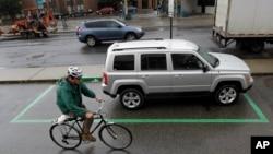 Seorang pengendara sepeda melewat sebuah mobil sewaan yang terparkir di Hoboken, New Jersey, 4 Juni 2012. (Foto: AP/ilustrasi)
