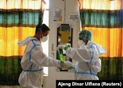 Para petugas kesehatan mengenakan alat pelindung diri (APD) bersiap menangani pasien COVID-19 di unit gawat darurat di Jakarta, 17 Juni 2021. (Foto: Ajeng Dinar Ulfiana/Reuters)