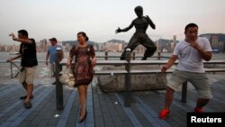 Tourists pose in front of a bronze statue of the late Kung Fu legend Bruce Lee on the waterfront facing Hong Kong island July 12, 2013.