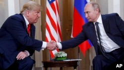 FILE - U.S. President Donald Trump, left, and Russian President Vladimir Putin, right, shake hands at the beginning of their meeting at the Presidential Palace in Helsinki, Finland, July 16, 2018.