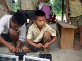 Boys help assemble an LED system