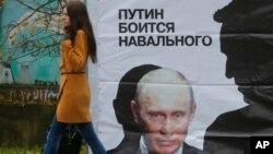 """Seorang perempuan melewati poster yang berbunyi """"Putin takut pada Navalny"""" di Kirov, Rusia (16/10/2013). Alexei Navalny adalah pemimpin oposisi dan juga blogger anti korupsi. Rusia memberlakukan UU Blogger tanggal 1/8/2014."""