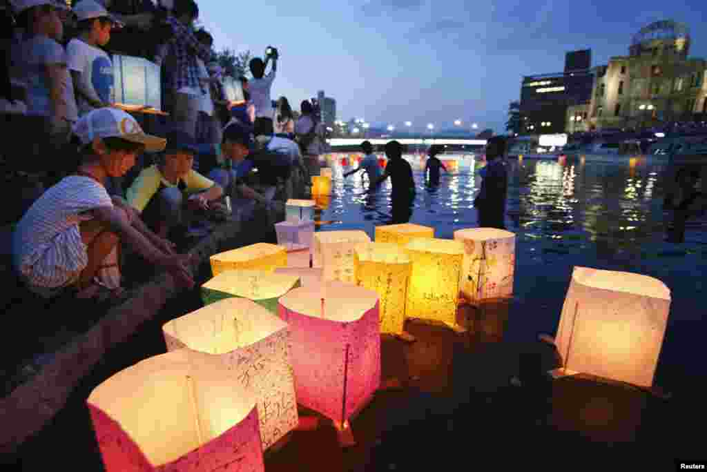 People release paper lanterns on the Motoyasu river facing the gutted Atomic Bomb Dome in remembrance of atomic bomb victims in Hiroshima, August 6, 2013. (Kyodo)
