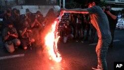 Một người biểu tình đốt cờ Mỹ bên ngoài đại sứ quán Hoa Kỳ ở Athens, Hy Lạp, hôm 14/4.