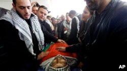 Mourners stand over the body of Palestinian Cabinet member Ziad Abu Ain, during his funeral in the West Bank city of Ramallah, Dec. 11, 2014.