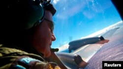 FILE - Sergeant Trent Wyatt looks out an observation window aboard a Royal New Zealand Air Force (RNZAF) P3 Orion maritime search aircraft as it flies over the southern Indian Ocean looking for debris from missing Malaysian Airlines flight MH370.