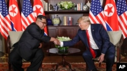 North Korea leader Kim Jong Un and U.S. President Donald Trump during their first meeting at the Capella resort on Sentosa Island Tuesday, June 12, 2018 in Singapore. (AP Photo/Evan Vucci)