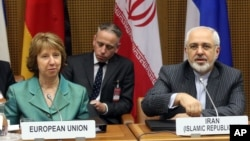 European Union foreign policy chief Catherine Ashton (L) and Iranian Foreign Minister Mohamad Javad Zarif (R) wait for the start of closed-door nuclear talks in Vienna, Austria, March 18, 2014.