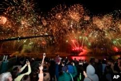 Warga di Brisbane, Australia, menyambut pengumuman Komite Olimpiade Internasional mengenai terpilihnya Brisbane sebagai tuan rumah Olimpiade 2032, dengan perayaan kembang api, Rabu, 21 Juli 2021. (AP)