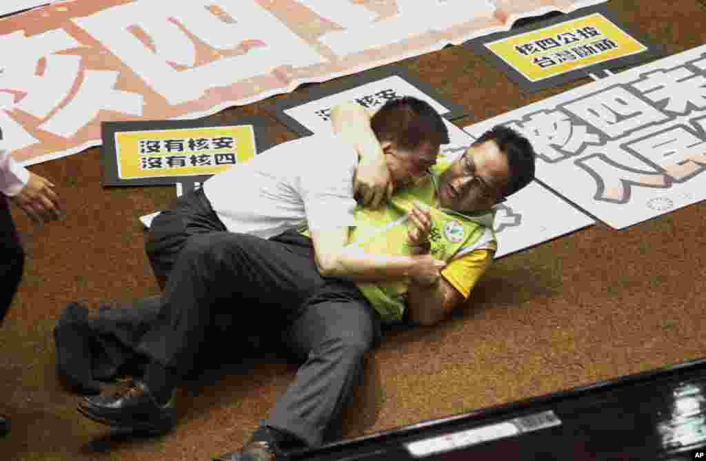 Ruling and opposition lawmakers fight each other on the legislature floor in Taipei, Taiwan. Taiwanese lawmakers exchanged punches and thrown water at each other ahead of an expected vote authorizing a referendum on whether to go ahead with the construction of a fourth power plant.