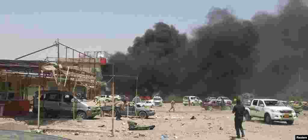 Smoke rises from the site of a car bomb attack in the town of Tuz Khormato, Iraq, June 9, 2014.