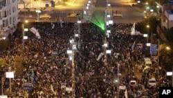 Các xe tăng của quân đội bảo vệ xung quanh dinh Tổng thống trong khi những người phản đối tập trung hô to các khẩu hiệu chống đối Tổng thống Morsi, Cairo, Ai Cập, 7/12/2012.