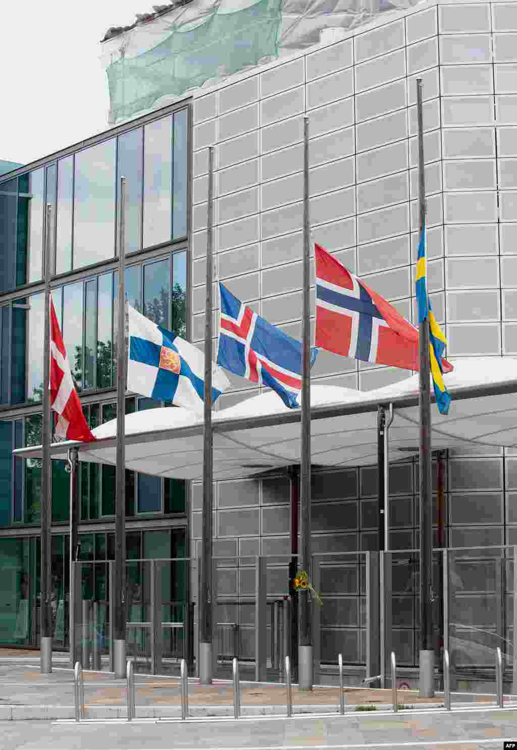 The flags of Scandinavian countries fly at half-staff in front of the Scandinavian and Nordic Embassies' building in Berlin, Germany, Saturday July 23, 2011. A Norwegian is reported to have set off an explosion in Oslo city centre before going on a shooti