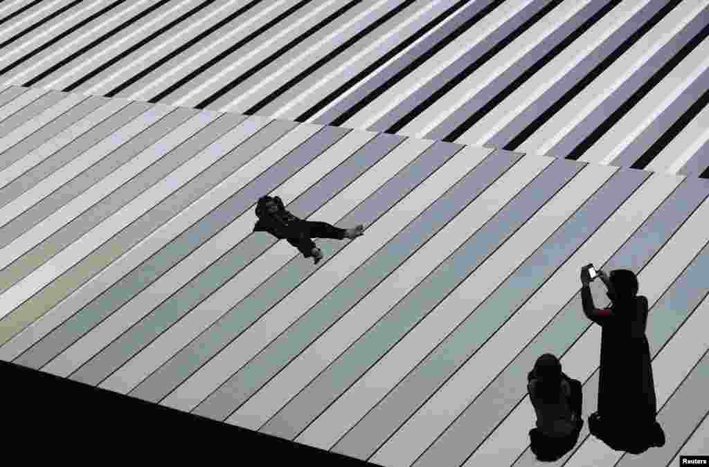A woman takes pictures of her son as he lies down on top of 'Test Pattern', an installation by Japanese artist Ryoji Ikeda, during its opening exhibition as part of Vivid Sydney, a creative festival of light, music and ideas, that runs until June 10.