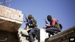 Militan dari Partai Pekerja Kurdi (PKK) sedang berlindung di balik tembok saat menyerang pasukan keamanan Turki di Nusaydin, Turki (1/3).