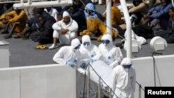 Những di dân sống sót ngồi trên tàu tuần duyên Bruno Gregoretti của Ý trong lúc thi thể người thiệt mạng được khiêng ra khỏi tàu tuần duyên Bruno Gregoretti của Ý tại Senglea, Valletta Grand Harbour, ngày 20 tháng 4, 2015.