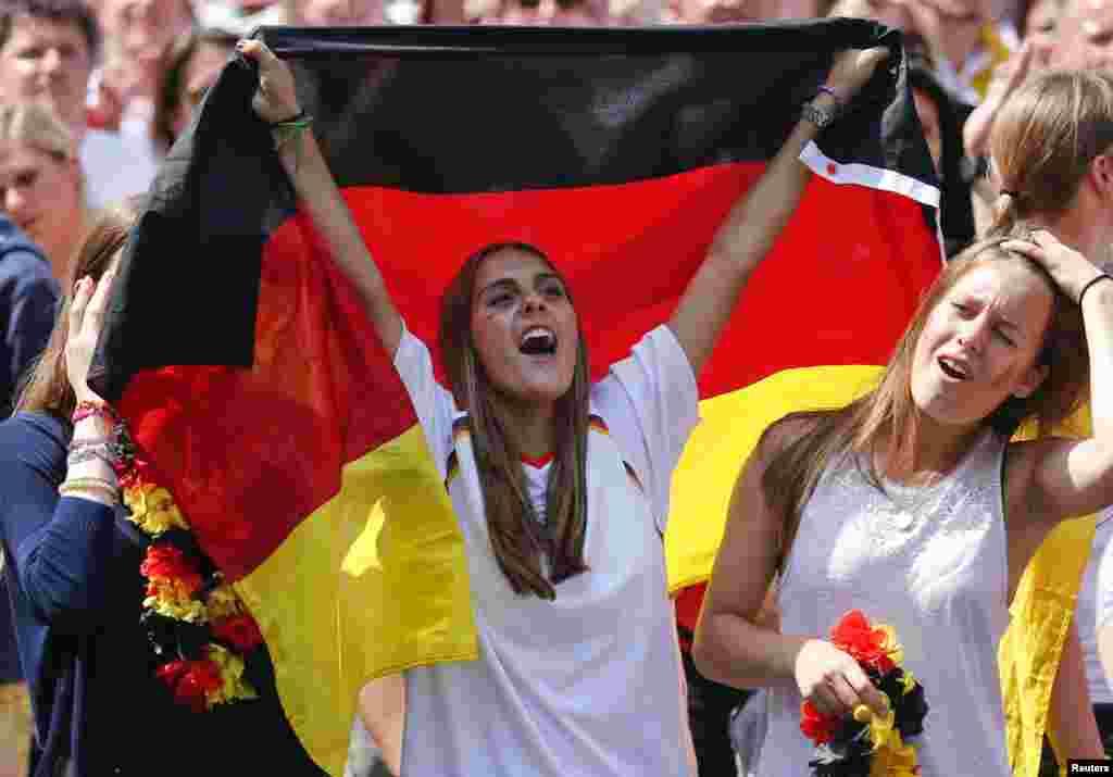 Para penggemar bola bersorak untuk tim sepakbola nasional Jerman ketika merayakan kemenangan tim tersebut dalam Piala Dunia Brazil 2014, di tempat nobar Fan Mile, di Berlin, 15 Juli 2014.
