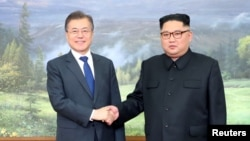 FILE - South Korean President Moon Jae-in shakes hands with North Korean leader Kim Jong Un during their summit at the truce village of Panmunjom, North Korea, May 26, 2018.