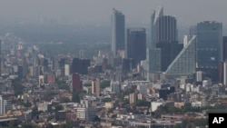 FILE - Haze hangs over Mexico City. Some two billion children live in regions where outdoor air pollution exceeds WHO's minimum air quality guidelines.