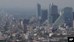 Haze hangs over Mexico City at midday, March 15, 2016. Despite the heavy downpours that come each rainy season, Mexico City has long struggled with providing enough water for some 21 million people in the greater metropolitan area.