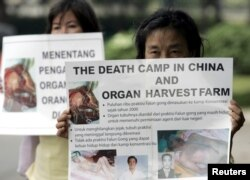 FILE - Indonesian Falun Gong followers carry placards during a protest in front of U.S. embassy in Jakarta, April 19, 2006. A group of protesters called on U.S. President George W. Bush to raise the issue of China harvesting organs from Chinese people during his talks with Chinese President Hu Jintao.