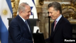 Argentina's President Mauricio Macri gives Israeli Prime Minister Benjamin Netanyahu a box with hard drives containing all of Argentina's government archives related to the Holocaust during a ceremony in Buenos Aires, Argentina Sept. 12, 2017.