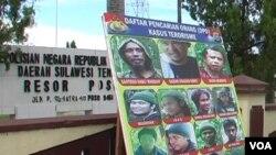 Baliho memuat daftar buronan kasus terorisme di depan markas kepolisian resor Poso. (VOA/Yoanes Litha)
