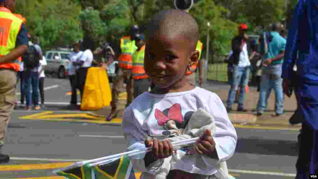 Un niño sale a la calle a ver pasar el cortejo. [Foto: Ramón Taylor, VOA].