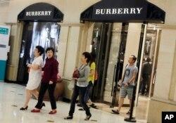 2012年6月,顾客走出英国奢侈品制造商博伯利(Burberry)在上海开设的分店。如今不少消费者花钱不再大手大脚