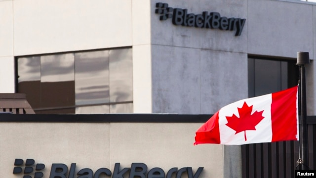 A Canadian flag waves in front of a Blackberry logo at the Blackberry campus in Waterloo, Sept. 23, 2013.