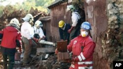 Hungarian rescue workers and fire fighters clean a yard flooded by toxic mud in Kolontar, Hungary, 7 Oct 2010
