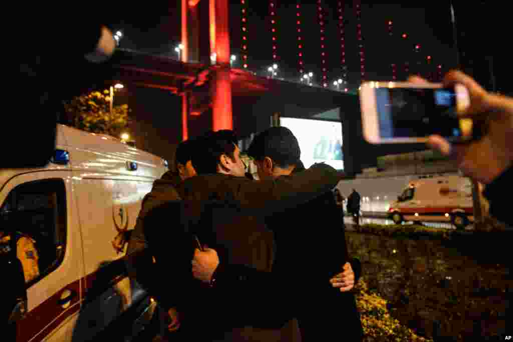 Youths embrace near the scene of an attack in Istanbul, early Jan. 1, 2017. An assailant believed to have been dressed in a Santa Claus costume and armed with a long-barreled weapon, opened fire at a nightclub in Istanbul's Ortakoy district.