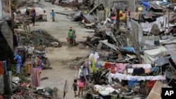 Survivors of Typhoon Haiyan walk amid ruins of their homes in Maraboth, Philippines, Thursday, Nov. 14, 2013. Typhoon Haiyan, one of the most powerful storms on record, hit the country's eastern seaboard on Friday, destroying tens of thousands of building